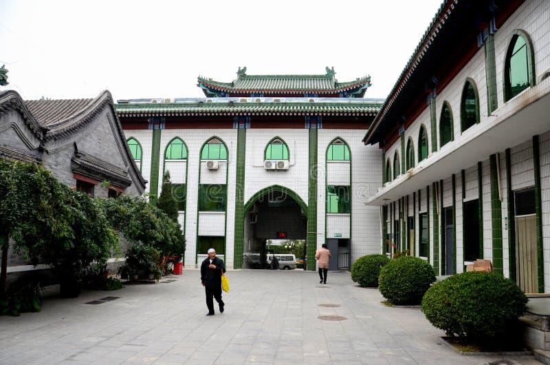 Den äldre kinesiska muslimska mannen går i ingångsborggård av moskéPeking Kina arkivfoton
