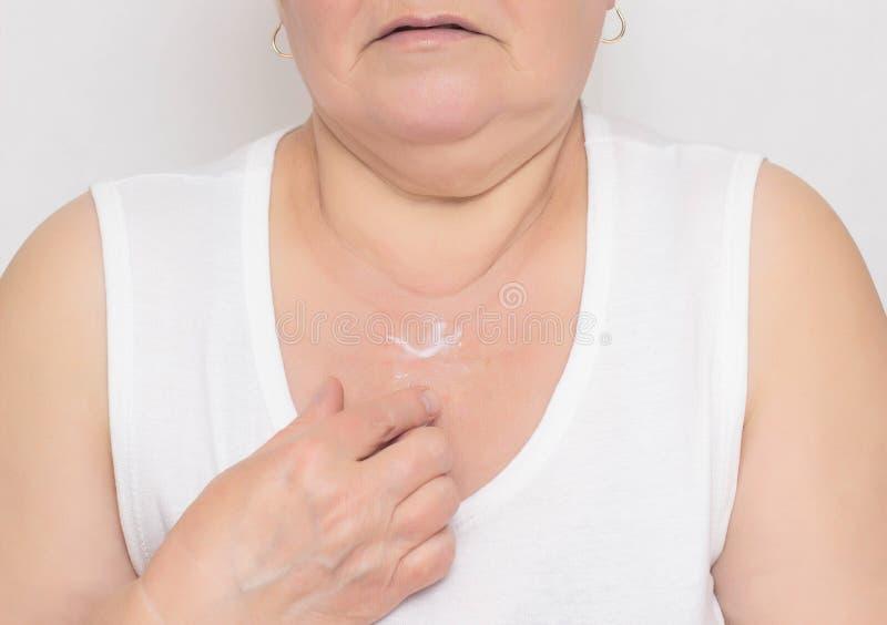 Den äldre kvinnan applicerar anti--skrynklan kräm i det decollete området för att föryngra och fukta torr hud, närbilden som anti arkivfoto