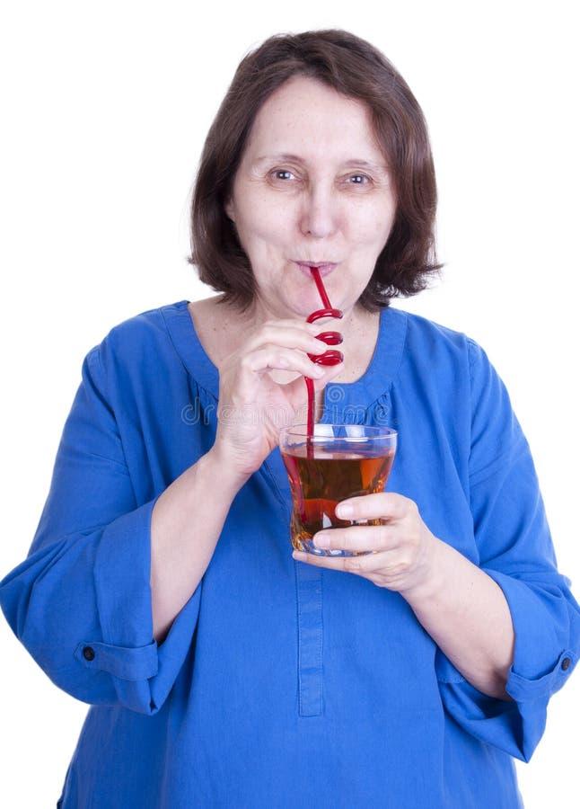 Den äldre kvinnan dricker fruktsaft arkivbild