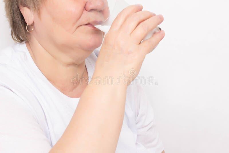 Den äldre kvinnan dricker vatten från ett exponeringsglas på en vit bakgrund, begrepp av förlust av kroppvätska i åldringen, utto royaltyfria bilder
