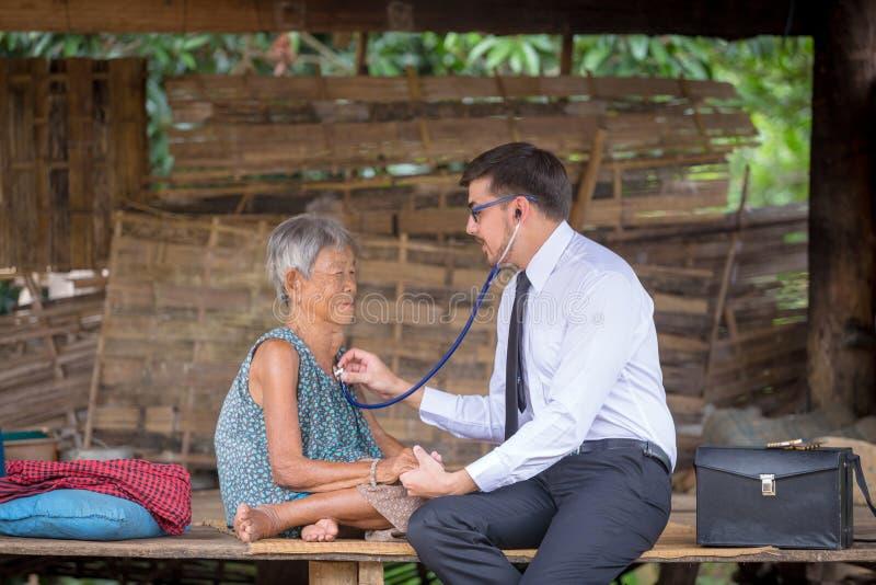 Den äldre kvinnan får besök från doktorn till det tålmodiga hemmet fotografering för bildbyråer