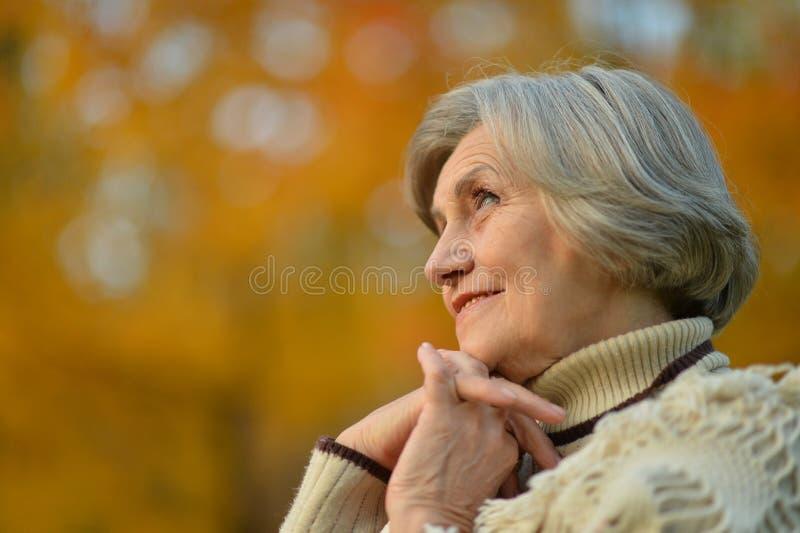 Den äldre kvinnan går i höst parkerar royaltyfri foto
