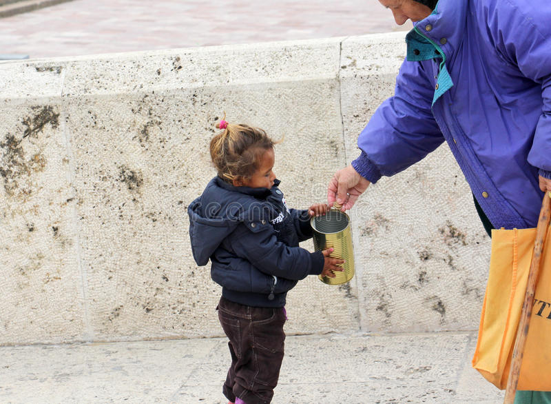 Den äldre kvinnan ger pengar till det gulliga tiggareflickacentret av Skopje, huvudstad av Makedonien arkivfoto