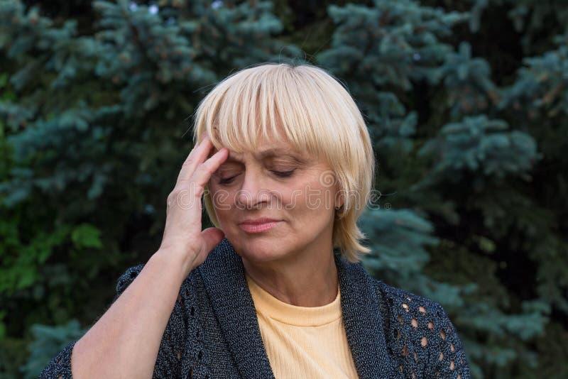 Den äldre kvinnan har en huvudvärk och trycker på hennes huvud arkivfoton