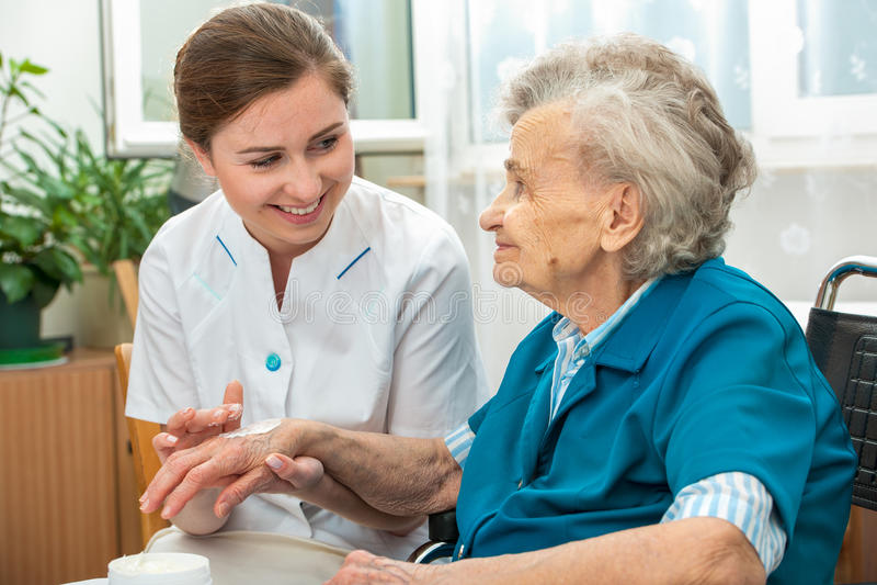 Den äldre kvinnan hjälps av sjuksköterskan hemma arkivbilder