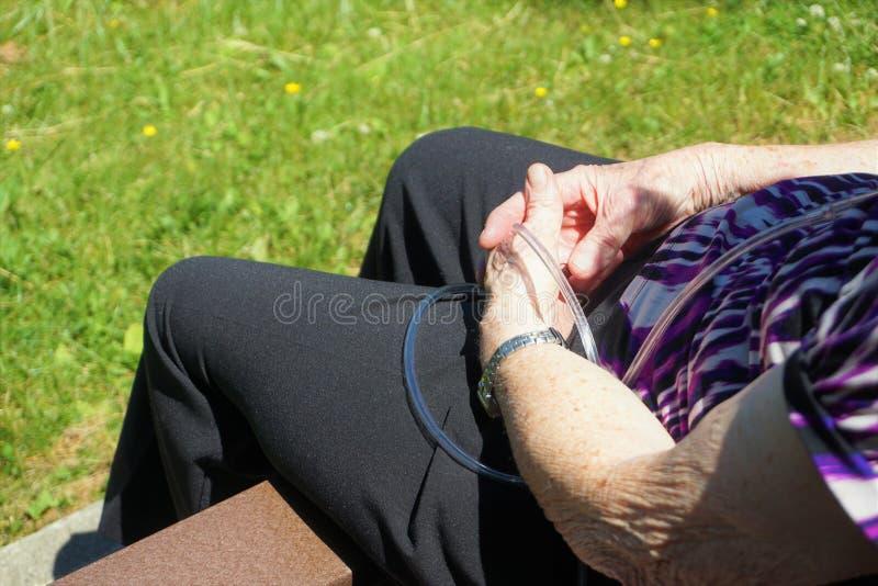 Den äldre kvinnan sitter på bänk med det bärbara syreröret arkivfoto