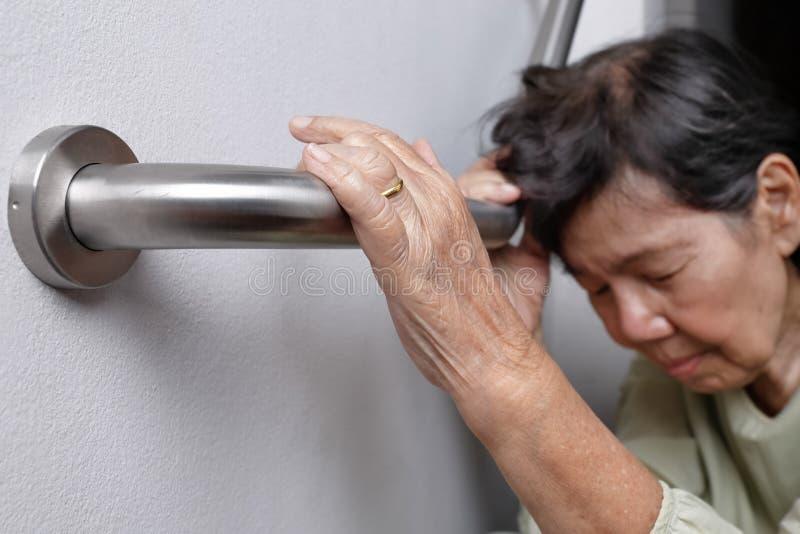 Den äldre kvinnan som är hållande på ledstången för säkerhet, går arkivfoton
