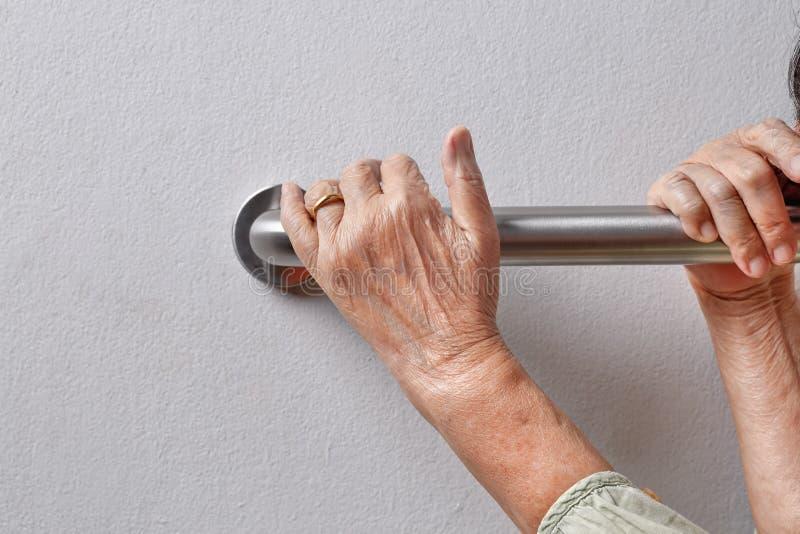 Den äldre kvinnan som är hållande på ledstången för säkerhet, går royaltyfri bild