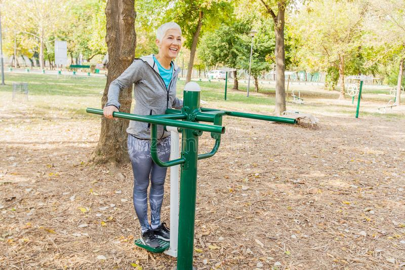 Den äldre kvinnan som övar på offentliga sportar, parkerar fotografering för bildbyråer