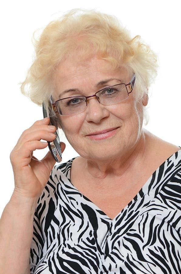 Den äldre kvinnan talar på telefonen arkivfoton