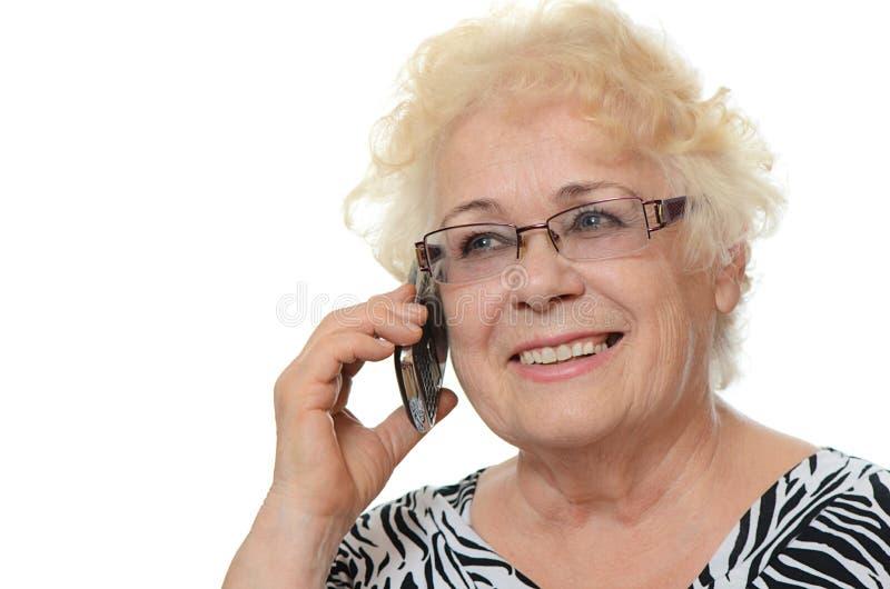 Den äldre kvinnan talar på telefonen royaltyfri fotografi
