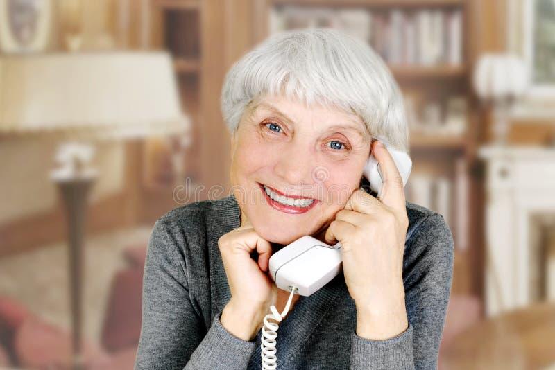 Den äldre kvinnan talar på telefonen, modern, farmor royaltyfria bilder