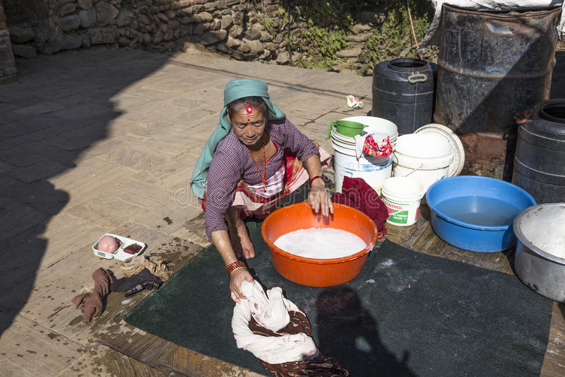Den äldre kvinnan tvättar den smutsiga tvätterit i Katmandu, Nepal arkivbilder