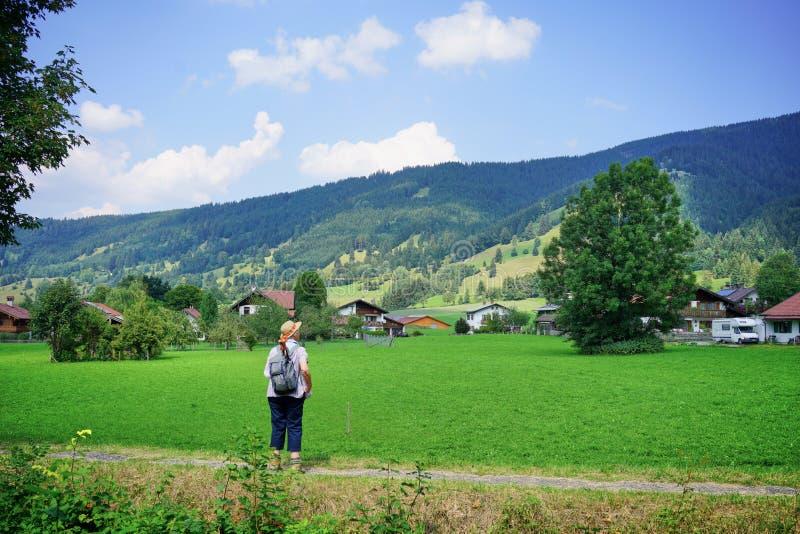 Den äldre kvinnliga fotvandraren tar i den bayerska bygden royaltyfri foto