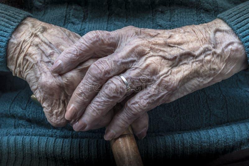 Den äldre kvinnlign räcker manikyr och rottingen royaltyfria bilder