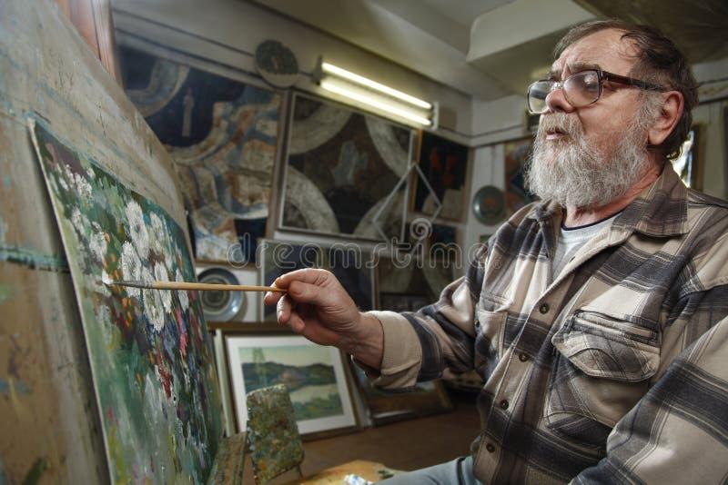 Den äldre målaren med skägget och exponeringsglas drar en blommabild vid olje- målarfärg i konstseminarium fotografering för bildbyråer
