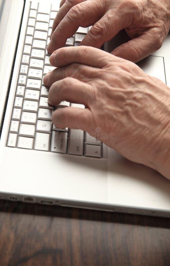 Den äldre mannen arbetar på bärbara datorn royaltyfri foto