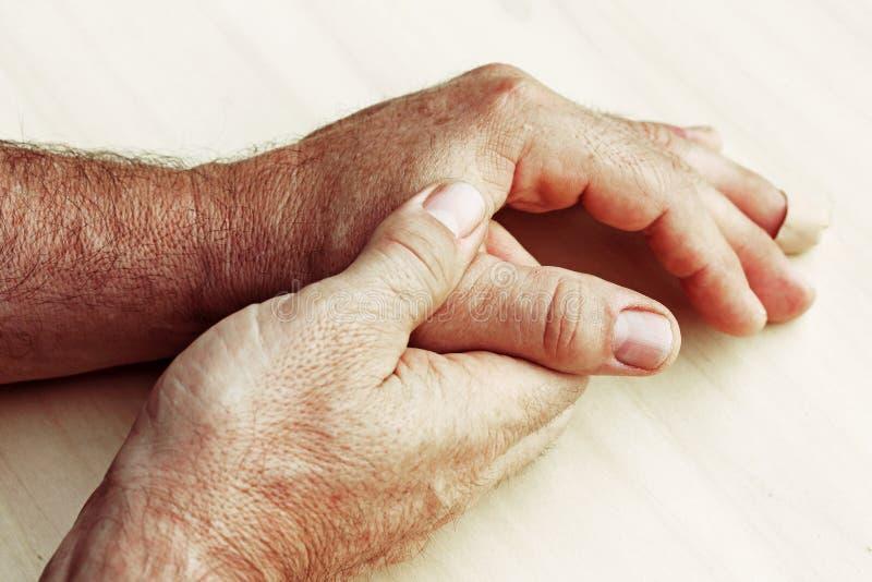 den äldre mannen har att smärta i fingrar och händer arkivfoton