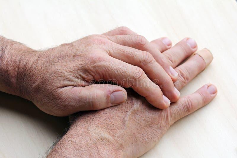 Den äldre mannen har att smärta i hans händer royaltyfri bild