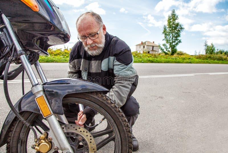 Den äldre mannen kontrollerar hans hjul för motorcykel` s royaltyfri fotografi