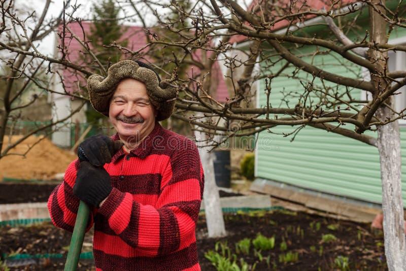 Den äldre mannen med ett trädgårds- hjälpmedel ger spetsar och trick för att arbeta royaltyfri foto
