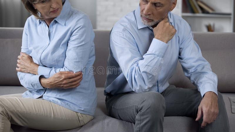 Den äldre mannen och kvinnan som sitter på soffan efter, grälar och att vända tillbaka till varandra royaltyfria bilder