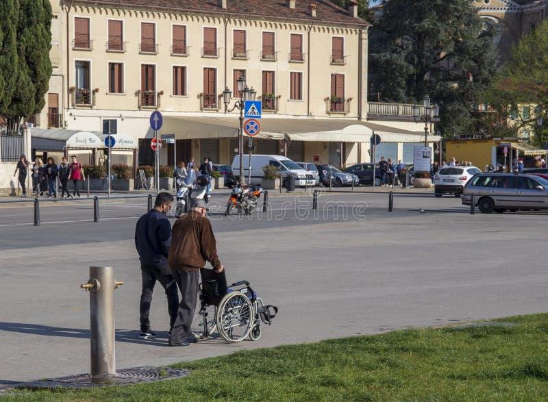 Den äldre mannen som hjälps av en pojke, skjuter han rullstolen royaltyfria foton