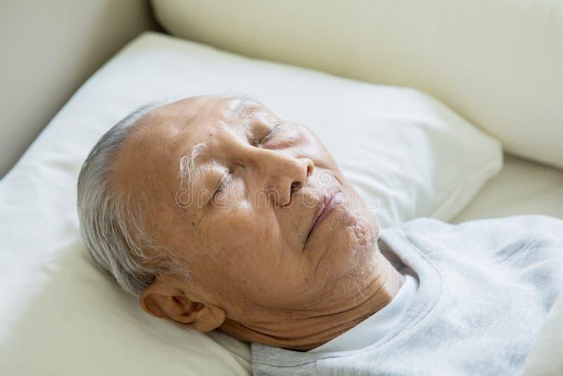 Den äldre mannen som vilar i säng med ögon, stängde sig royaltyfri foto