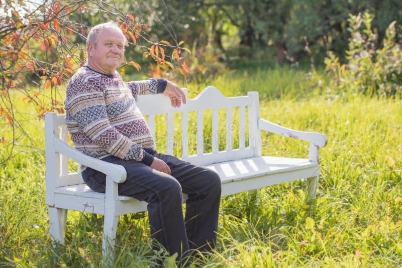 Den äldre mannen som vilar på den vita bänken i höst, parkerar royaltyfria bilder