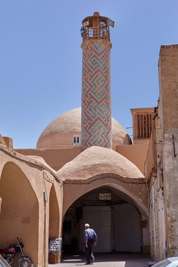 Den äldre muselmanen skriver in i lerabyggnad med minaret, Yazd, Iran royaltyfri foto