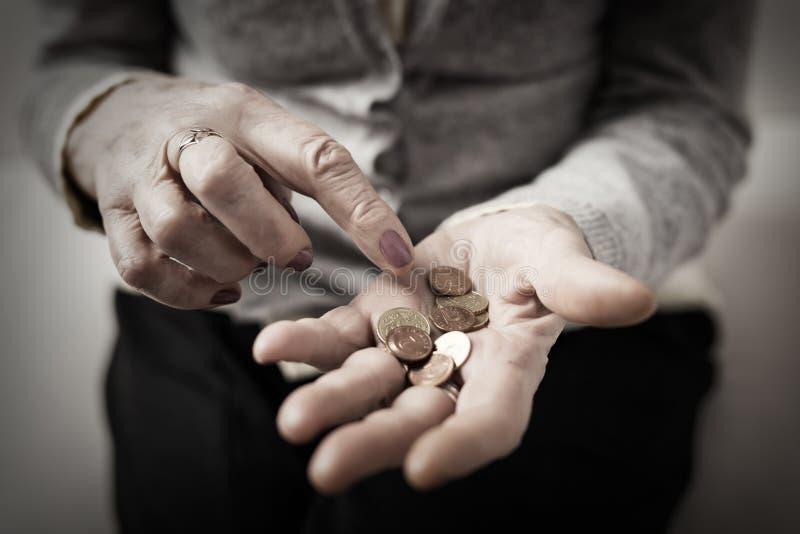 Den äldre personen som räknar pengar i henne, gömma i handflatan royaltyfria bilder