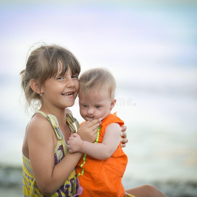 Den äldre systern rymmer en härlig flicka med Down Syndrome royaltyfria bilder