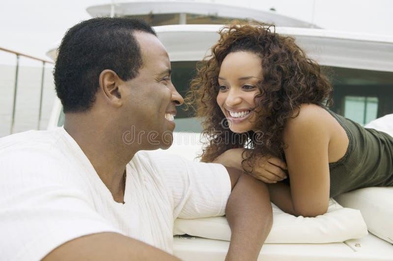 Den älska afrikansk amerikan kopplar ihop på yachten fotografering för bildbyråer