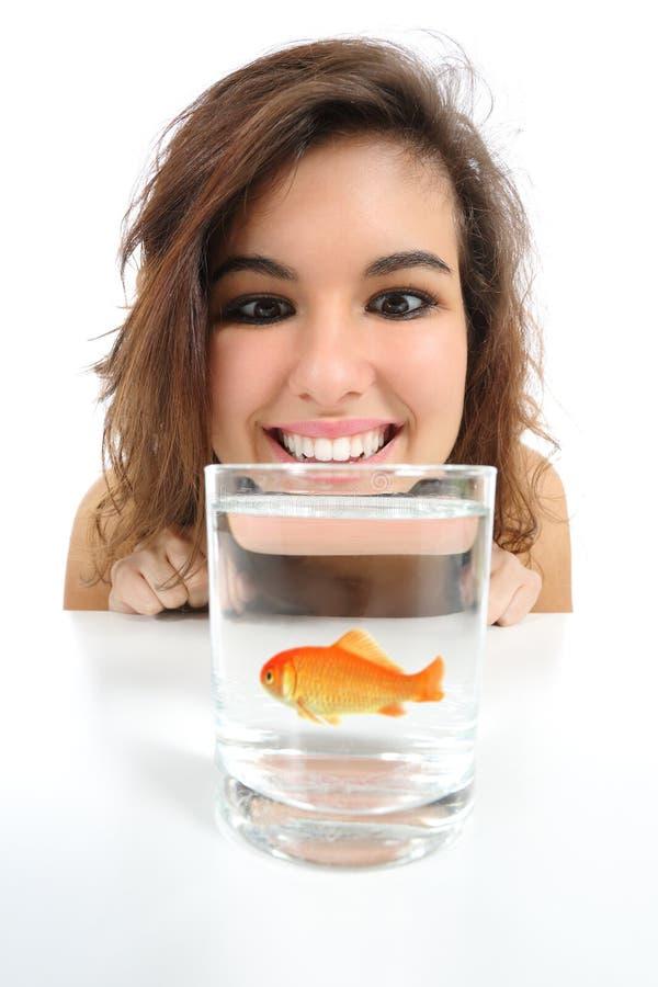 Den älsklings- fisken i ett exponeringsglas behöver omsorg och en kvinna som ser den royaltyfria foton