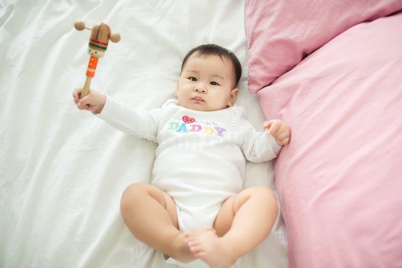 Den älskvärda asiatet behandla som ett barn flickasammanträde på säng på hennes rum arkivfoto
