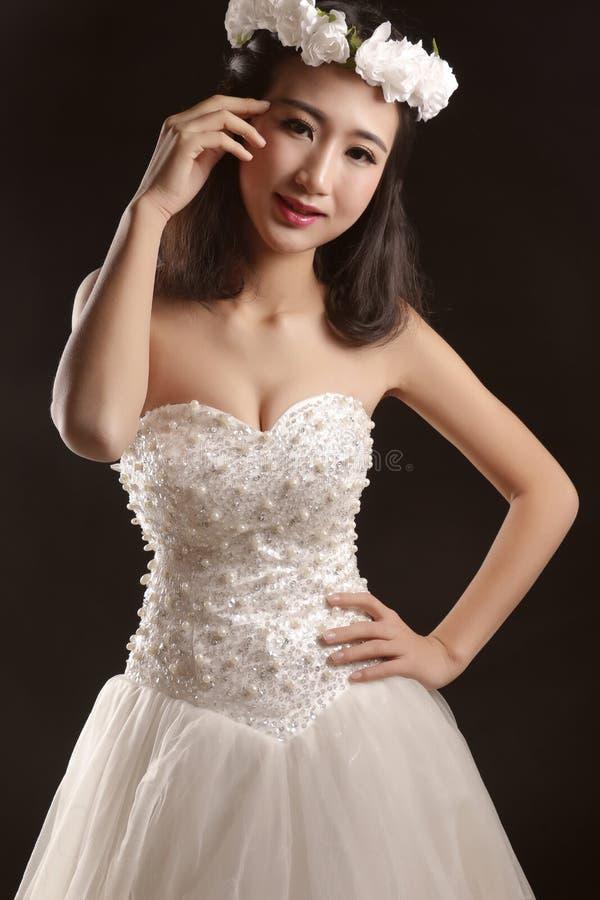 Den älskvärda bruden i bröllopsklänningen arkivfoton