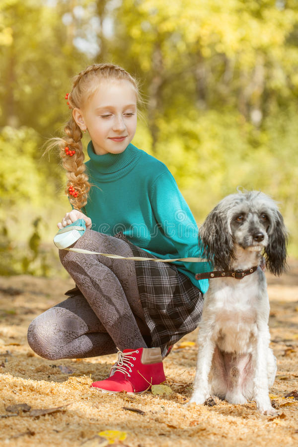 Den älskvärda flickan som går med hunden i höst, parkerar royaltyfri fotografi