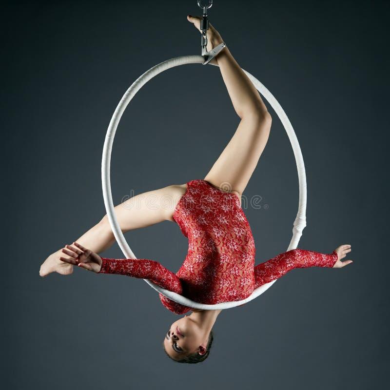 Den älskvärda gymnasten utför akrobatiskt jippo på beslag arkivfoton