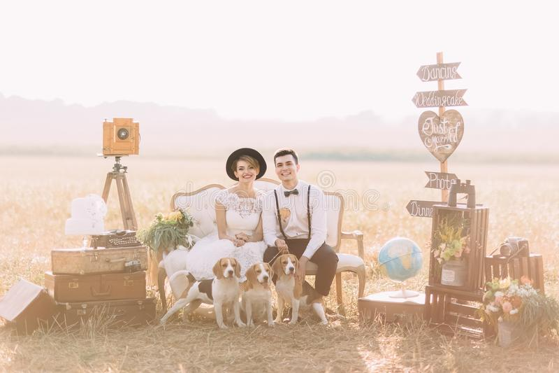 Den älskvärda horisontalståenden av de tappning klädde nygifta personerna som sitter med hundkapplöpningen på soffan som omges me fotografering för bildbyråer
