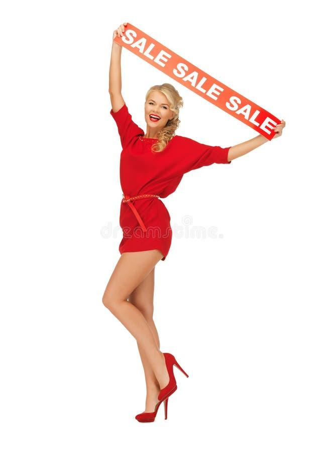 Den älskvärda kvinnan i röd klänning med rea undertecknar royaltyfri fotografi