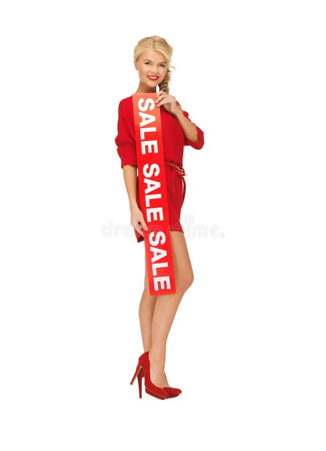 Den älskvärda kvinnan i röd klänning med rea undertecknar arkivfoto