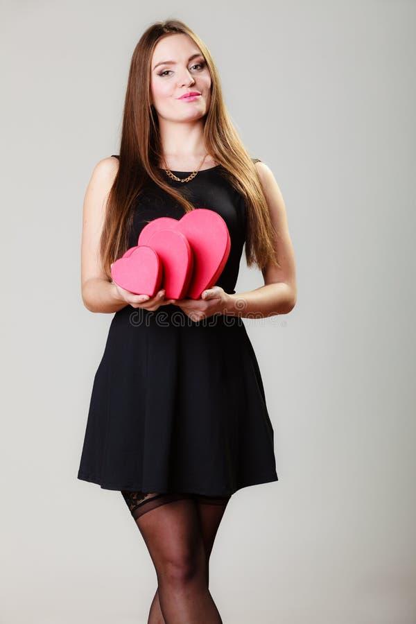 Den älskvärda kvinnan med röd hjärta formade gåvaaskar arkivfoton