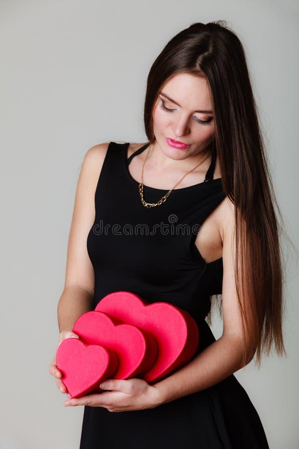 Den älskvärda kvinnan med röd hjärta formade gåvaaskar royaltyfri foto