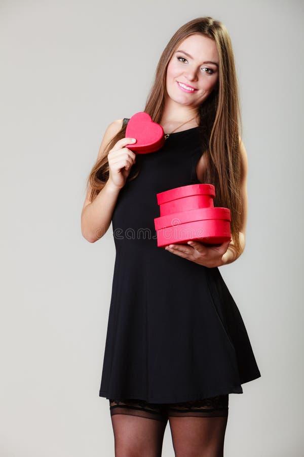 Den älskvärda kvinnan med röd hjärta formade gåvaaskar royaltyfri fotografi