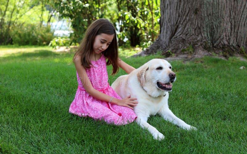 Den älskvärda lilla flickan med hennes bästa hundvän på parkerar under sommar i Michigan royaltyfri bild