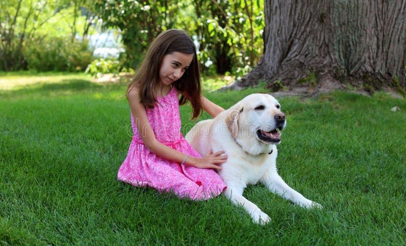 Den älskvärda lilla flickan med hennes bästa hundvän på parkerar under sommar i Michigan royaltyfria foton