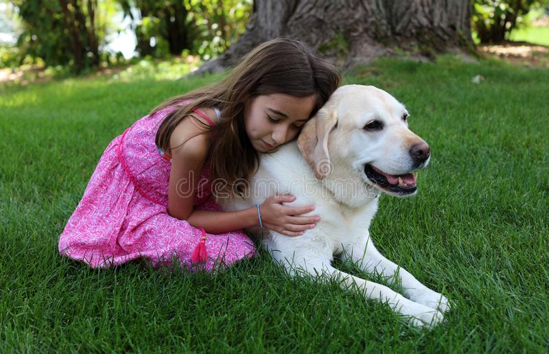 Den älskvärda lilla flickan med hennes bästa hundvän på parkerar under sommar i Michigan royaltyfri foto