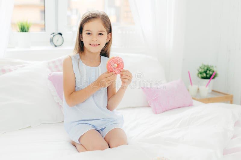 Den älskvärda lilla flickan rymmer den läckra munken i händer som går att ha frukosten, poserar på säng i hemtrevligt vitt sovrum arkivbilder