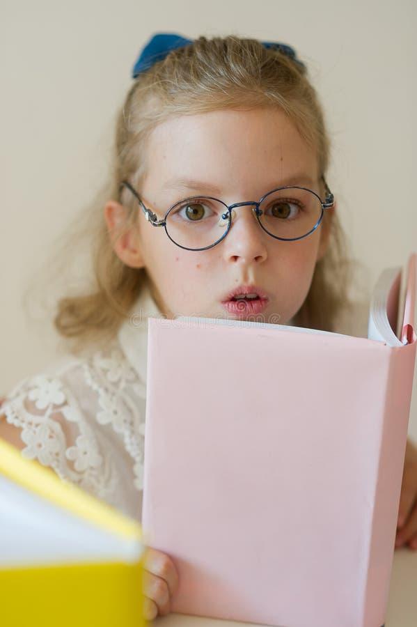 Den älskvärda lilla studenten läser royaltyfri foto