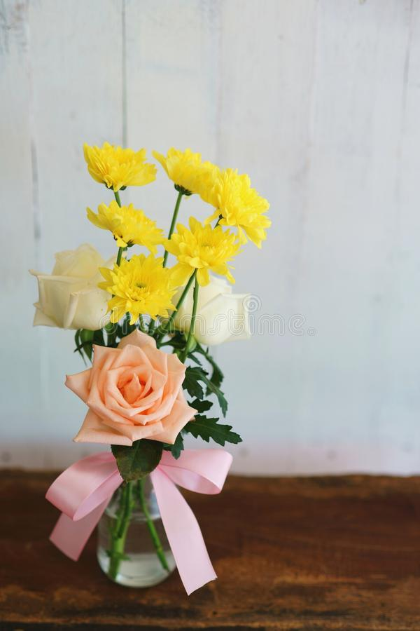 Den älskvärda lillfingerblomningen steg i vas på trätabellen med vit väggbakgrund, sött gåvabegrepp arkivbild